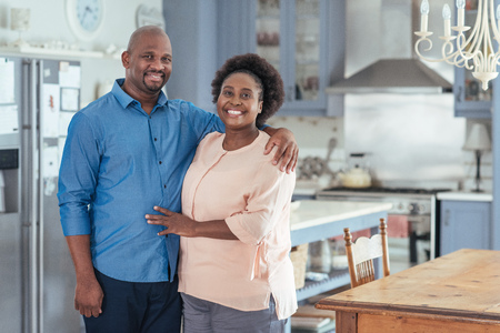 Smiling African couple standing together in their kitchen