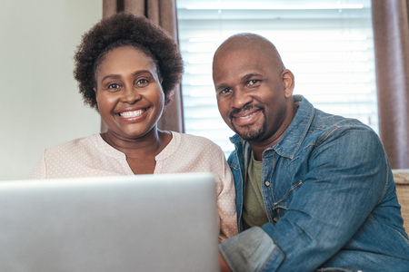 Smiling African couple sitting at home together using a laptop