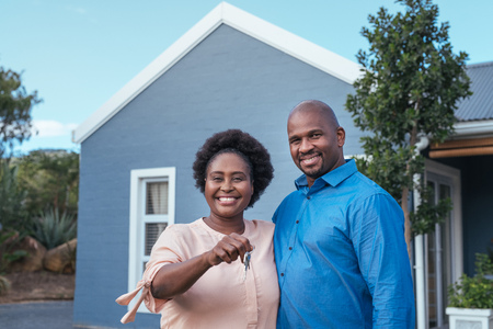 Smiling African couple standing with keys to their new home