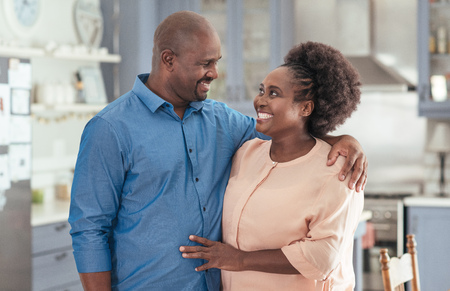 Mature African couple standing affectionately together in their kitchen Stock Photo - 87962211