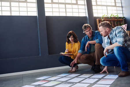 Focused coworkers discussing paperwork layed out on an office floor