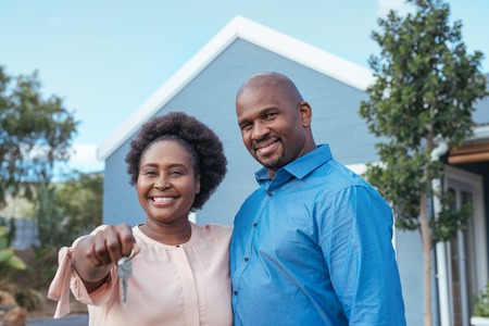 Smiling African couple holding the keys to their new home