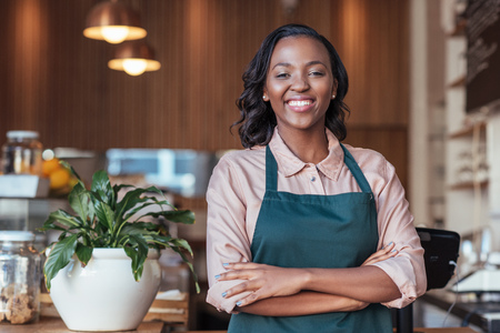 Smiling African entrepreneur standing at the counter of her cafe Stock Photo