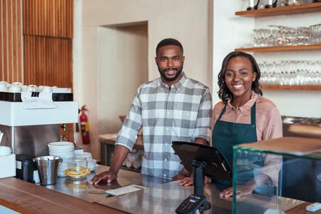 Sonriendo empresarios africanos de pie en el mostrador de su panadería