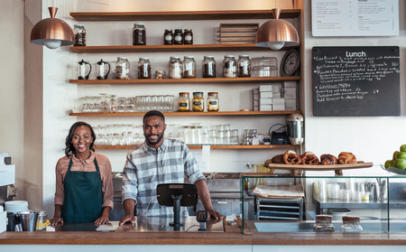 Two smiling African entrepreneurs standing behind their bakery counter