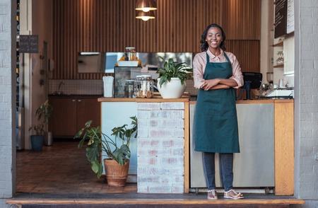Smiling African entrepreneur standing welcomingly in front of her cafe