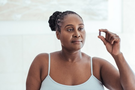 Anxious African woman looking at a pill in her hand