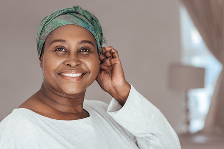 Happy adult African woman wearing on a stylish headscarf Stock Photo