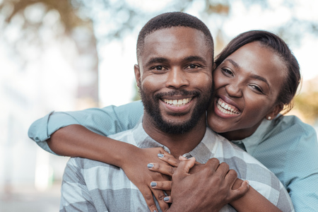 Affectionate young African couple standing outside on a sunny day Foto de archivo