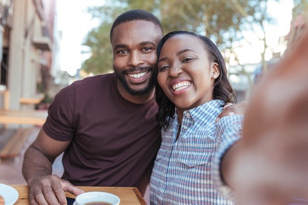Smiling young African couple taking selfies together at a cafe 版權商用圖片
