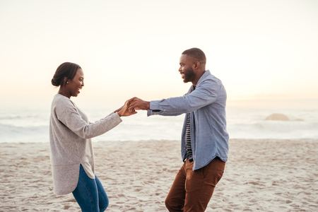 Smiling young African couple dancing on a beach at sunset Stock Photo