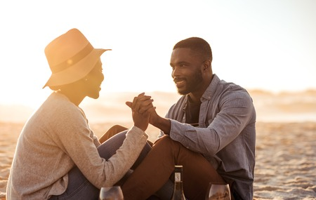 Smiling young African couple sitting on a beach at dusk Stock Photo - 90802749