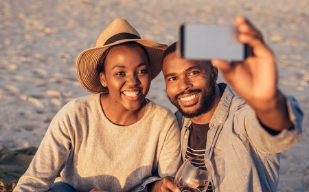 Happy young African couple taking selfies together at the beach Stock Photo