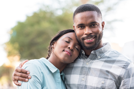 Happy young African couple standing outside on a sunny day