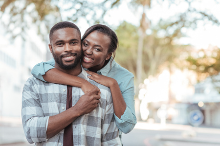 Content African couple standing together outside on a sunny day