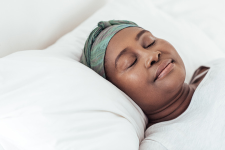 Young African woman wearing a headscarf asleep in bed