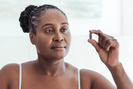 African woman looking at a pill in her hand
