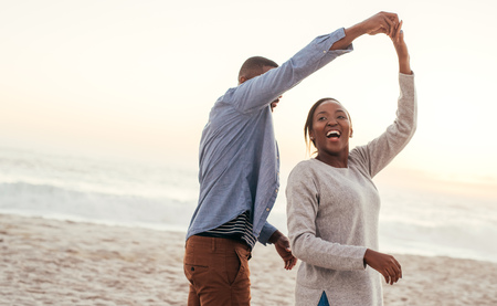 Laughing African couple dancing together on a beach at sunset