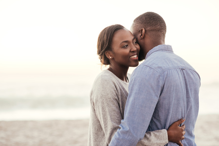Young African woman embracing her husband at the beach