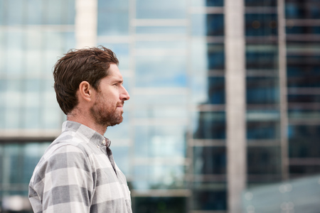 Profile of a young man standing alone in the city Stock Photo