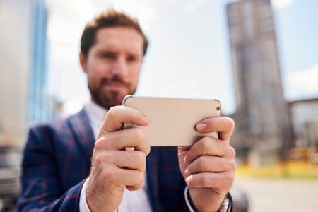 Young businessman standing in the city using his smartphone