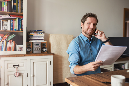 Man reading documents and talking on a cellphone at home