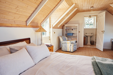 Spacious attic bedroom with bathroom in a home Stock Photo