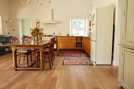 Área de comedor y cocina en una casa de estilo rústico. Foto de archivo