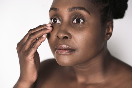 Beautful young African woman feeling the skin around her eyes