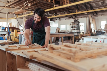Skilled artisan hand sanding wood in his large workshop