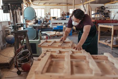 Skilled woodworker sanding furniture in his large workshop