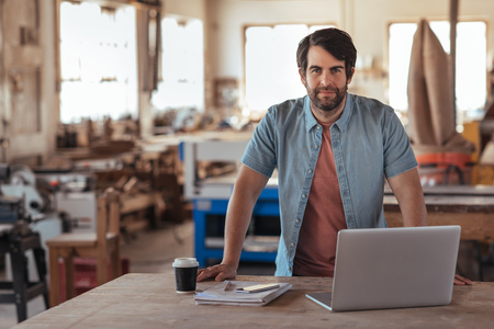 Confident young craftsman using a laptop in his workshop