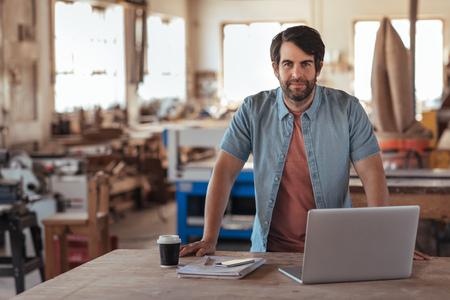 Pewny siebie młody rzemieślnik korzystający z laptopa w swoim warsztacie