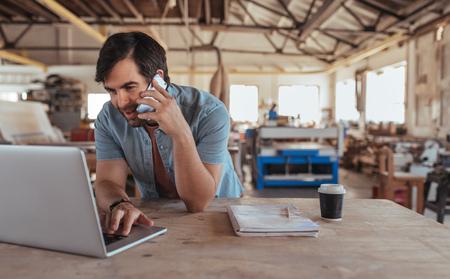 Sonriente joven carpintero trabajando en un banco en su gran taller trabajando en línea con una computadora portátil y discutiendo diseños con un cliente en un teléfono celular