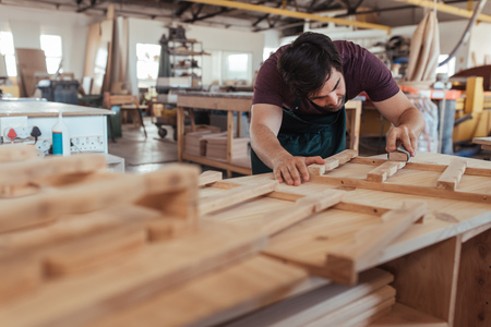 Skilled craftsman hand sanding pieces of wood in his workshop Stock Photo