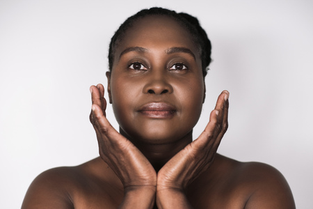 Mature African woman with perfect skin against a white background
