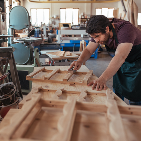 Craftsman skillfully sanding wood while working in his carpentry studio
