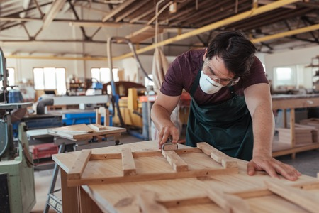 Craftsman in protective workwear sanding wood in his workshop Stock Photo