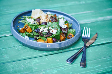 Delicious mixed salad sitting on a rustic turquoise wooden table Stockfoto
