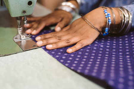 Closeup of a seamstress stitching cloth with her sewing machine