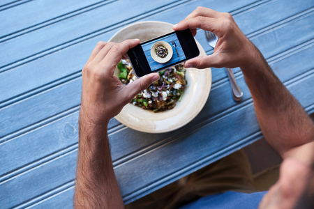 Man taking photos of his salad at a blue table Stock Photo