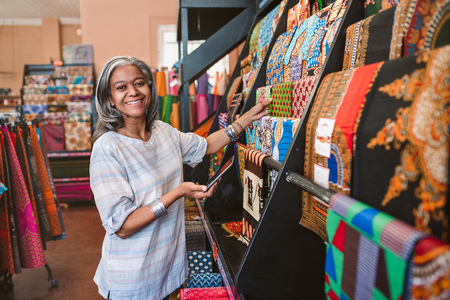 Smiling mature woman looking at colorful fabric in her shop Reklamní fotografie