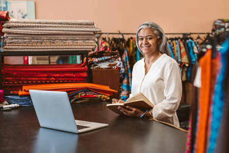 Smiling mature woman at work in her colorful fabric store