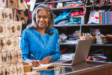Smiling woman working at the counter of her fabric shop Stockfoto