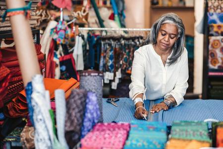 Mature woman marking cloth in her fabric shop before cutting 版權商用圖片