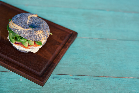 Cream cheese and salmon bagel on a rustic turquoise table