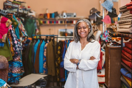 Mature woman smiling while standing in her fabric shop