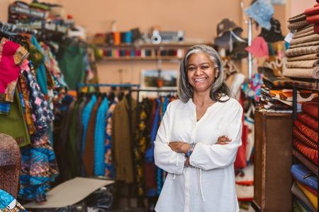 Mujer madura sonriendo mientras está de pie en su tienda de telas