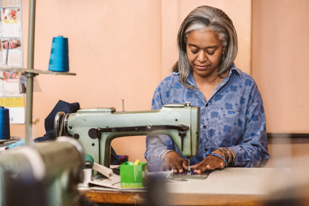 Mature seamstress working on a sewing machine in her workshop