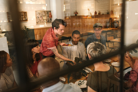 Waiter serving food to customers inside a trendy bistro